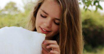 Pige spiser candyfloss fra candyfloss maskine