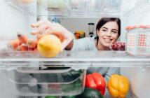 Kvinde tager en citron i et Electrolux køleskab
